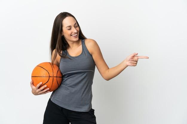 측면에 손가락을 가리키고 제품을 제시하는 격리 된 흰색 배경 위에 농구를하는 젊은 여자