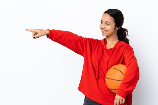 Молодая женщина играет в баскетбол на изолированном белом фоне, указывая пальцем в сторону и представляет продукт