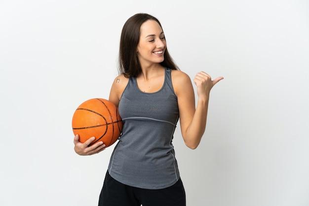 제품을 제시하는 측면을 가리키는 격리 된 흰색 배경 위에 농구를하는 젊은 여자