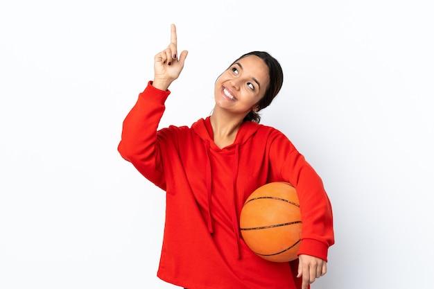 검지 손가락으로 좋은 아이디어를 가리키는 격리 된 흰색 배경 위에 농구를하는 젊은 여자