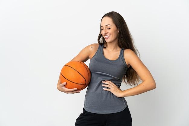 腰に腕と笑顔でポーズをとって孤立した白い背景の上にバスケットボールをする若い女性