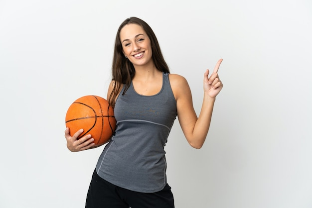 격리 된 흰색 배경 위에 농구를하는 젊은 여자가 보여주는 최고의 기호에 손가락을 들어 올려