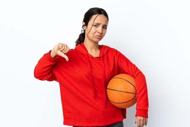 두 손으로 아래로 엄지 손가락을 보여주는 격리 된 흰색 배경 위에 농구를하는 젊은 여자