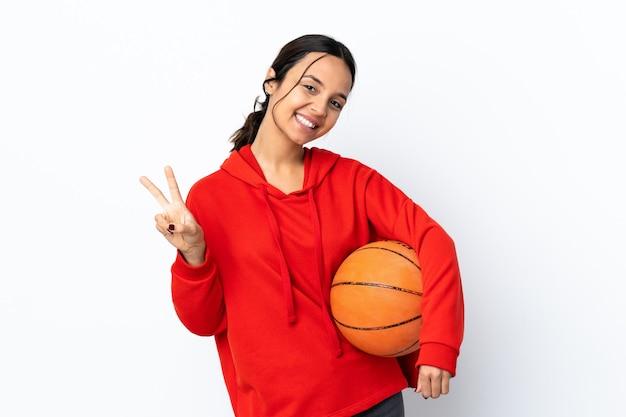 양손으로 승리 기호를 보여주는 격리 된 흰색 배경 위에 농구를하는 젊은 여자