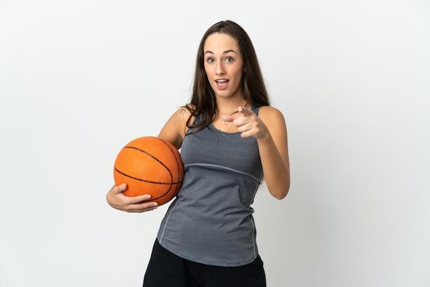 孤立した白い背景の上でバスケットボールをしている若い女性は驚いて正面を指しています