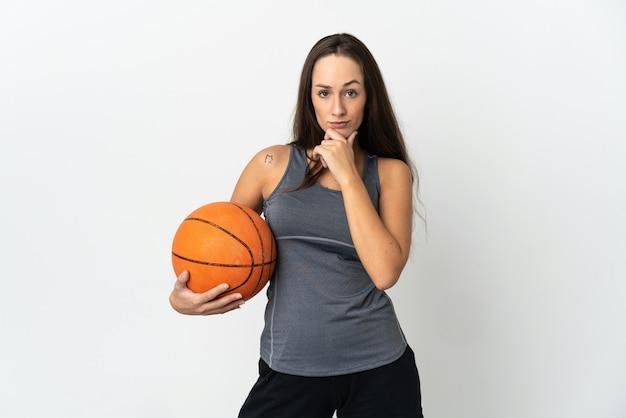 孤立した白い背景の思考でバスケットボールをする若い女性