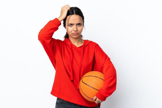 Молодая женщина играет в баскетбол на изолированном белом фоне с выражением разочарования и непонимания
