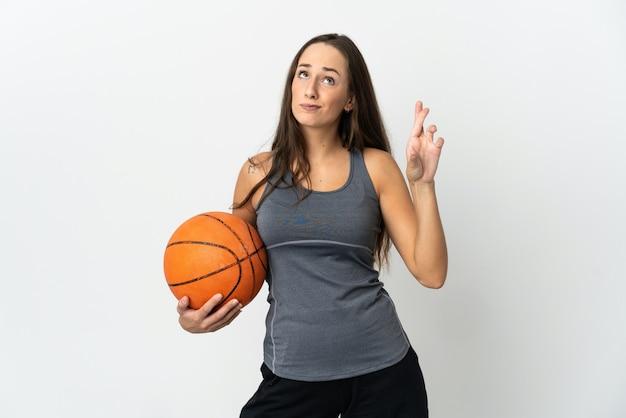 손가락을 건너고 최고를 바라는 격리 된 흰색 배경 위에 농구를하는 젊은 여자