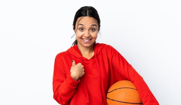 놀람 표정으로 격리 된 흰색 배경 위에 농구를하는 젊은 여자