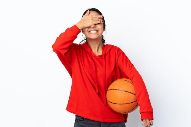 손으로 눈을 덮고 웃고 격리 된 흰색 위에 농구를하는 젊은 여자