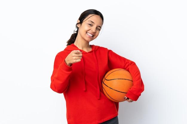 電話のジェスチャーをし、正面を指して孤立した白の上にバスケットボールをする若い女性