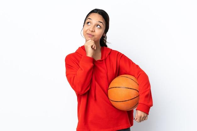찾는 동안 아이디어를 생각하는 격리 된 흰색 위에 농구를하는 젊은 여자