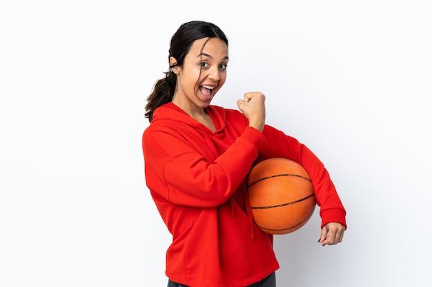 Молодая женщина играет в баскетбол над изолированной белой стеной, празднует победу