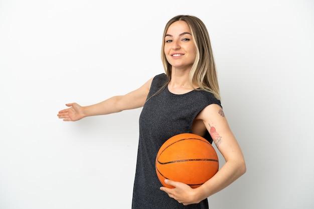 외진 흰 벽 너머로 농구를 하는 젊은 여성이 초대하기 위해 손을 옆으로 뻗고 있다