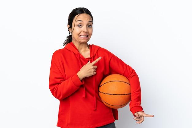 孤立した白い壁の上でバスケットボールをしている若い女性はおびえ、横を指しています