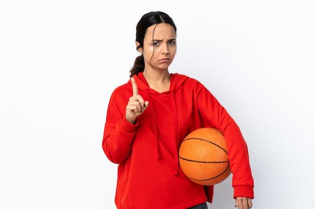 欲求不満と正面を指して孤立した白い壁の上でバスケットボールをしている若い女性