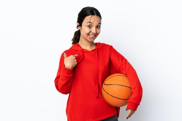 Молодая женщина играет в баскетбол над изолированной белой стеной, показывая большой палец вверх