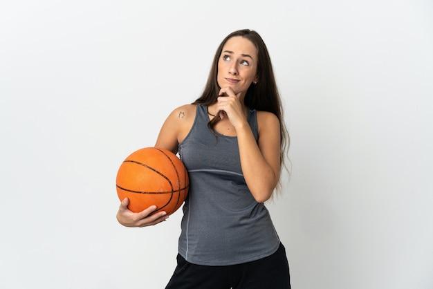 Молодая женщина играет в баскетбол над изолированной белой стеной, сомневаясь и думая