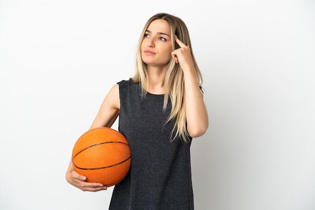 疑いと思考を持っている孤立した白い壁の上でバスケットボールをしている若い女性