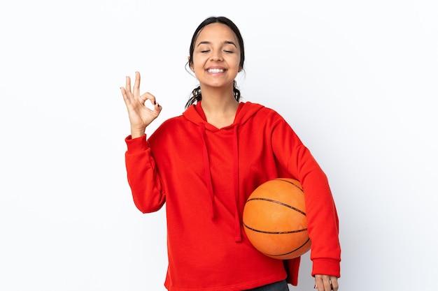 젠 포즈에서 격리 된 흰 벽에 농구를하는 젊은 여자