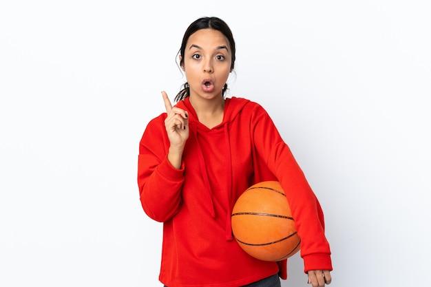Молодая женщина играет в баскетбол над изолированной белой стеной, намереваясь реализовать решение, подняв палец вверх