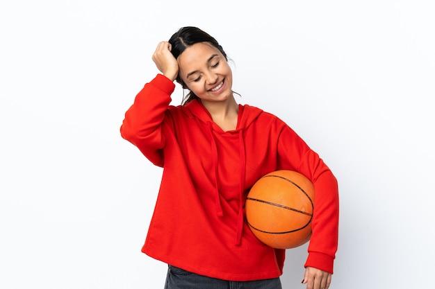 Молодая женщина играет в баскетбол над изолированной белой стеной, смеясь
