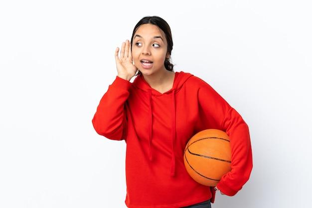 귀에 손을 넣어 뭔가를 듣고 격리 된 흰 벽에 농구를하는 젊은 여자