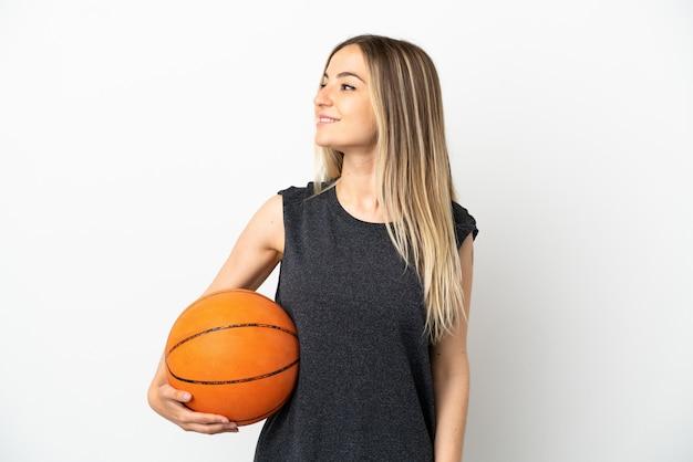 측면을 찾고 격리 된 흰 벽에 농구하는 젊은 여자