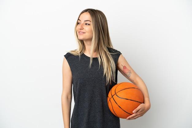 横を見て笑っている孤立した白い壁の上でバスケットボールをしている若い女性