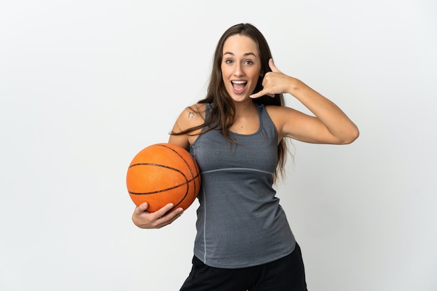 電話ジェスチャーを作る孤立した白い壁の上でバスケットボールをしている若い女性。コールバックサイン