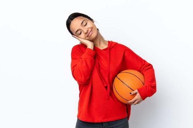 Dorable 식에서 수면 제스처를 만드는 격리 된 흰 벽에 농구를하는 젊은 여자