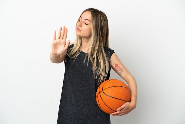 孤立した白い壁の上でバスケットボールをしている若い女性がジェスチャーを停止し、失望している