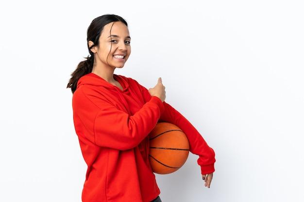 Молодая женщина играет в баскетбол над изолированной белой стеной, указывая назад