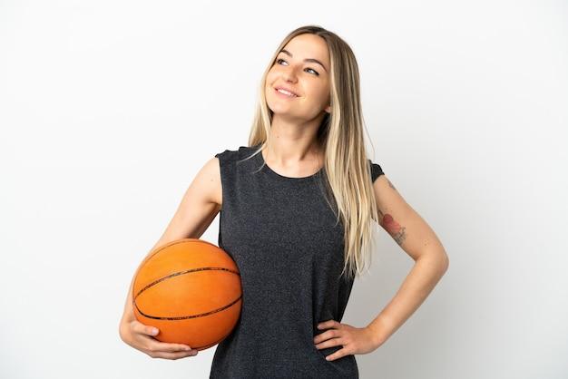 腰に腕と笑顔でポーズをとって孤立した白い壁の上でバスケットボールをしている若い女性