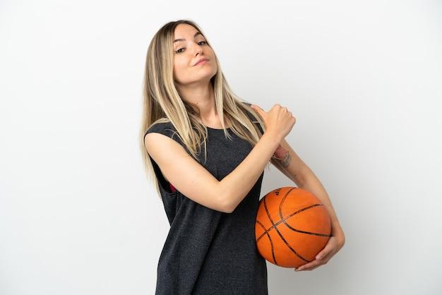 誇りと自己満足の孤立した白い壁の上でバスケットボールをする若い女性