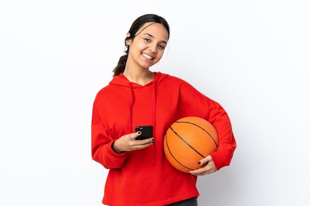 モバイルでメッセージを送信する孤立した白い壁の上でバスケットボールをしている若い女性