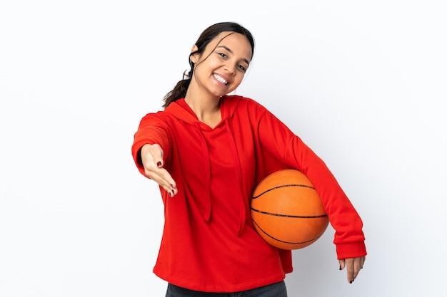 かなり閉じるために握手孤立した白い壁の上でバスケットボールをしている若い女性