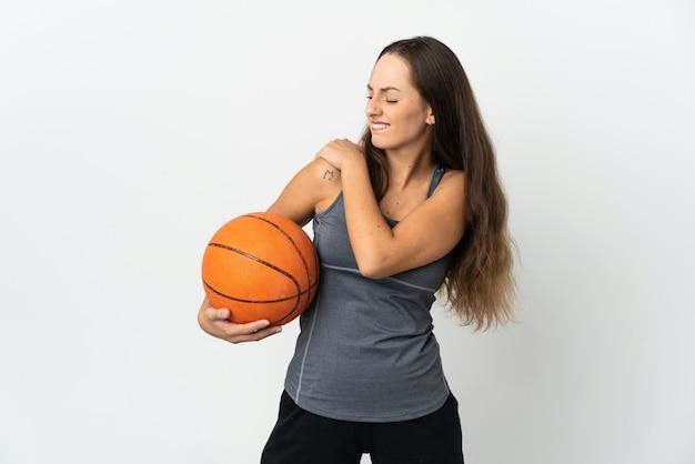 努力したために肩の痛みに苦しんで孤立した白い壁の上でバスケットボールをしている若い女性