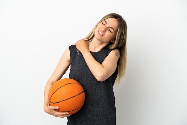 Молодая женщина, играющая в баскетбол над изолированной белой стеной, страдает от боли в плече из-за того, что приложила усилие