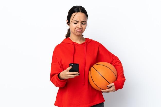孤立した白い壁の思考とメッセージを送信してバスケットボールをしている若い女性