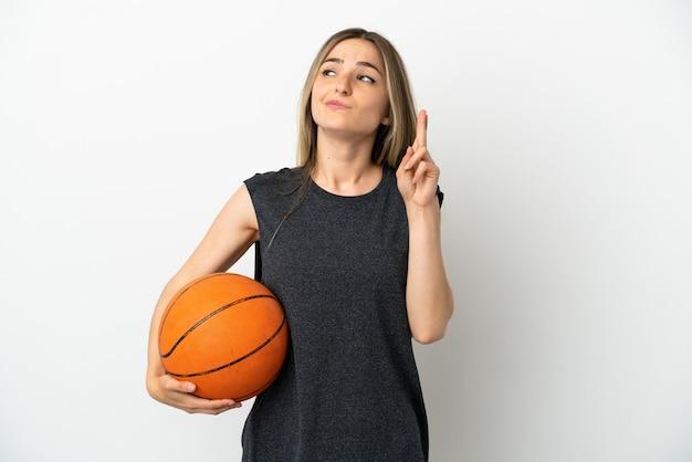 指が交差し、最高を願って孤立した白い壁の上でバスケットボールをしている若い女性