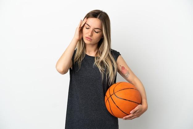 頭痛と孤立した白い壁の上でバスケットボールをする若い女性