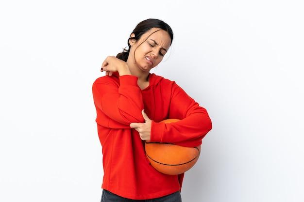팔꿈치에 통증이 격리 된 흰 벽에 농구를하는 젊은 여자