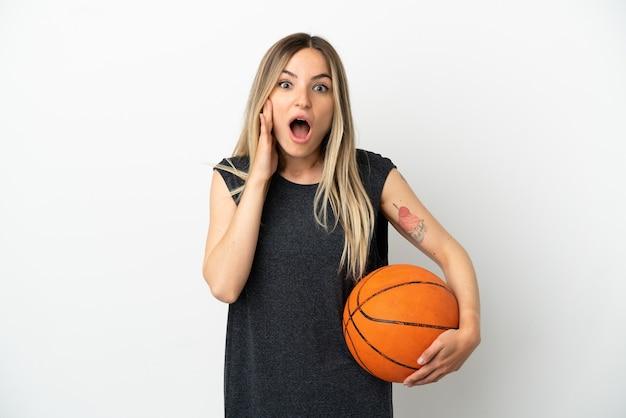 驚きとショックを受けた表情で孤立した白い壁の上でバスケットボールをしている若い女性