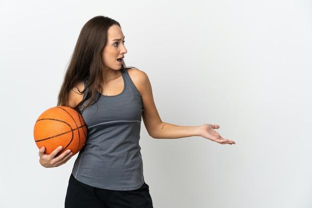 Молодая женщина играет в баскетбол над изолированной белой стеной с удивленным выражением лица, глядя в сторону