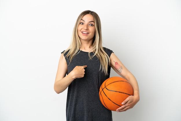 놀란 표정으로 고립된 흰 벽 너머로 농구를 하는 젊은 여자