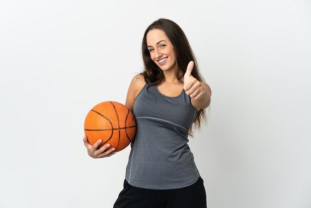 Молодая женщина играет в баскетбол над изолированной белой стеной с большими пальцами руки вверх, потому что произошло что-то хорошее