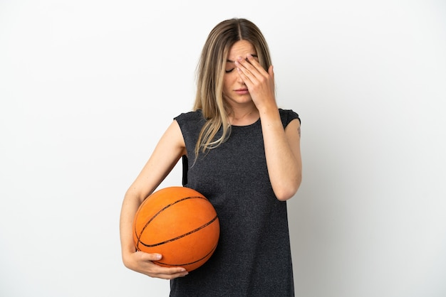 疲れたと病気の表情で孤立した白い壁の上でバスケットボールをしている若い女性