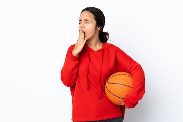 Молодая женщина играет в баскетбол над изолированной белой стеной, зевая и прикрывая широко открытый рот рукой