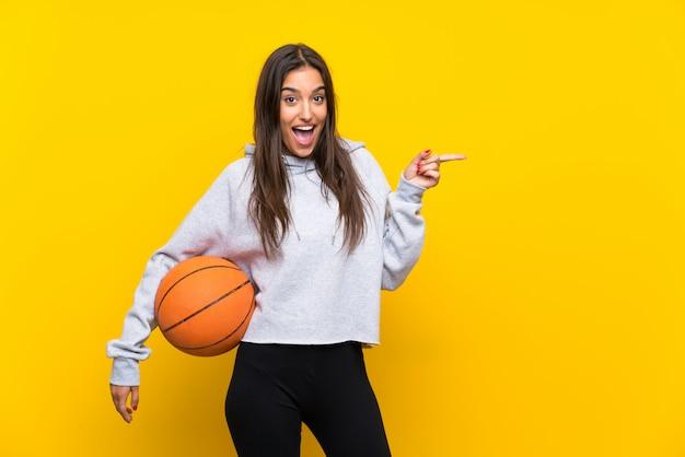 Молодая женщина играет в баскетбол на изолированной желтой стене удивлен и указывая пальцем в сторону